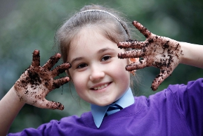 Girl with compost on hands